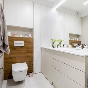 Biel, beż i dekory drewna to baza wystroju łazienki. Projekt: Joanna Nawrocka. Fot. Łukasz Bera