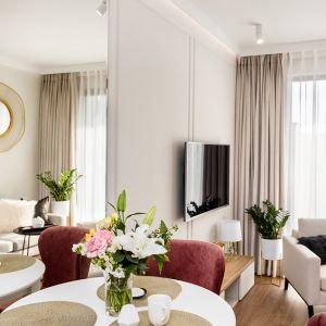 Lustrzana tafla na ścianie za stołem optycznie powiększa wnętrze. Projekt: Joanna Nawrocka. Fot. Łukasz Bera