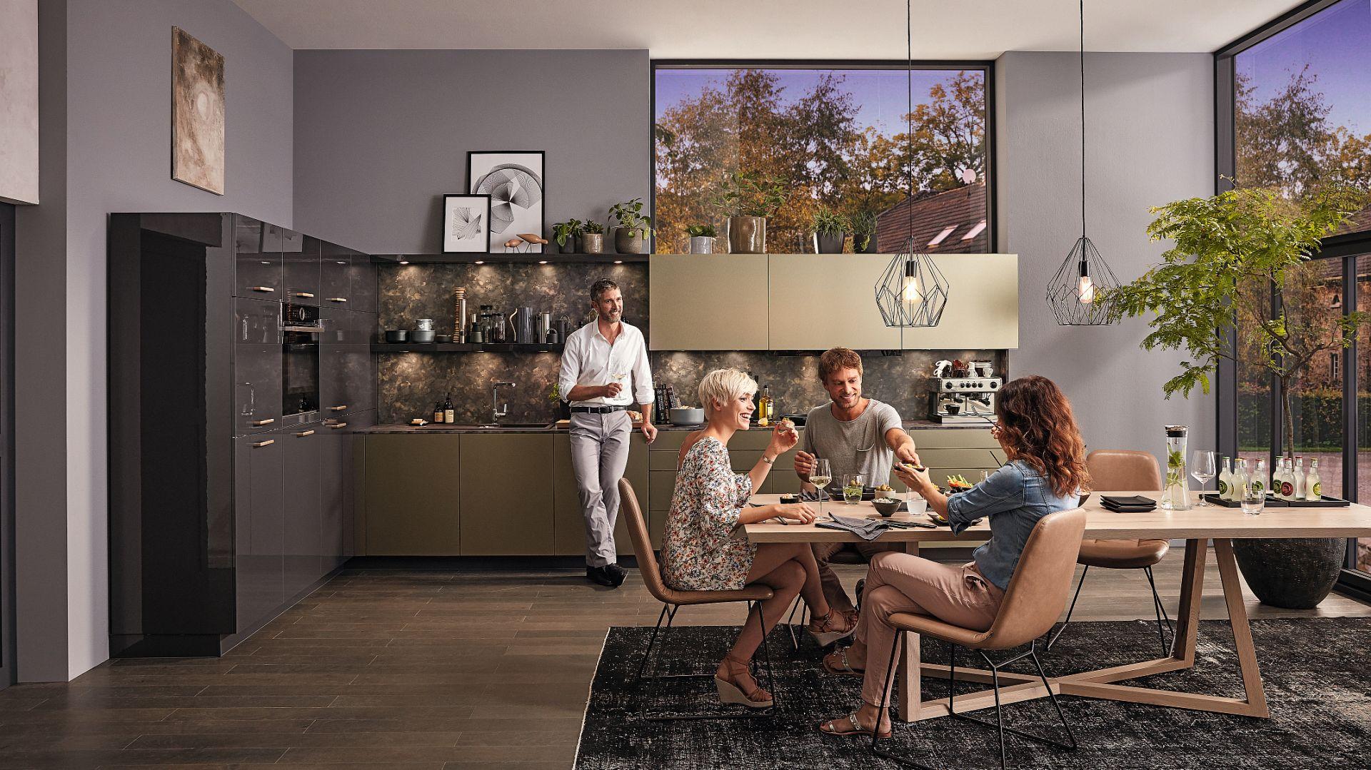 Kuchnia z programu Alnoglint, Alnopearl to połączenie eleganckich grafitowych frontów w połyskującym wykończeniu wysokiej zabudowy meblowej z matowymi frontami w złotym metalicznym kolorze. Fot. Alno