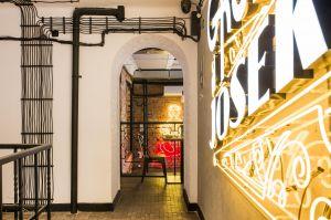 Do poszczególnych pomieszczeń prowadzą korytarze, które nawiązują do wąskich, bocznych uliczek Warszawy – sugeruje to zwłaszcza oświetlenie, stylizowane na uliczne latarnie. Projekt: THE SPACE. Fot. Piotr Czaja