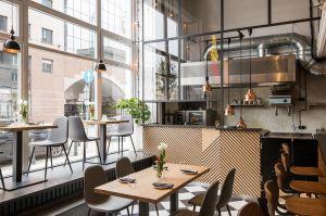 O ile na parterze mieści się jedna duża przestrzeń dla gości wraz z barem i kuchnią, o tyle na piętrze do mniejszych pomieszczeń prowadzi nas antresola oraz wąskie korytarze. Projekt: THE SPACE. Fot. Piotr Czaja