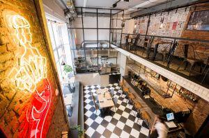 W całym koncepcie pojawiło się wiele odwołań historycznych - zaczynając od menu, strojów kelnerów, a kończąc na neonie - stylizowanych Warszawą i jej herbem. Projekt: THE SPACE. Fot. Piotr Czaja