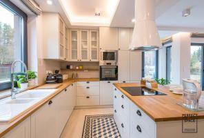 Spore okno nad zlewozmywakiem zapewnia odpowiednią ilość dziennego światła, zaś matowobiałe szafki nie przytłaczają wnętrza. Projekt i zdjęcia: Perfect Space