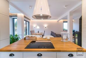 Od strony jadalni granicę kuchni wyznacza przestronna wyspa, okolona na podłodze wzorzystymi płytkami, niczym dywanem. Projekt i zdjęcia: Perfect Space