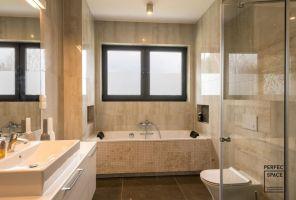 W przestronnej łazience wykorzystano kilka rodzajów płytek imitujących kamień. Wszystkie utrzymane są w beżowej tonacji. Projekt i zdjęcia: Perfect Space