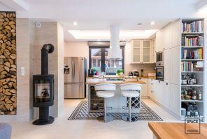 Część kuchenną ulokowano nieco na uboczu, w przestronnej niszy. Przestrzeń wydziela zabudowa w kształcie litery L. Projekt i zdjęcia: Perfect Space