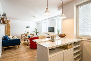 Zastąpienie ścianki oddzielającej oba pomieszczenia nowoczesną kuchenną wyspą, pozwoliło otworzyć i powiększyć przestrzeń dzienną. Projekt i zdjęcia: Perfect Space