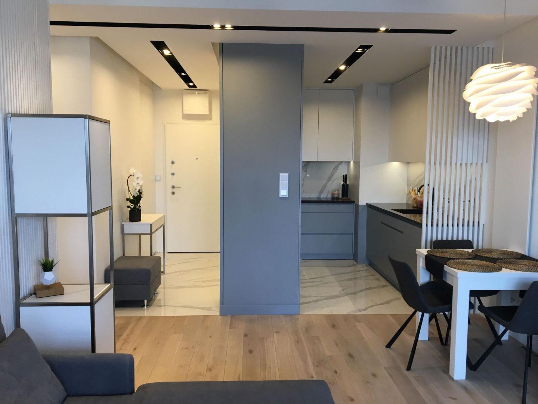 Mieszkanie składa się z czterech pomieszczeń: salonu połączonego z aneksem kuchennym i holem, sypialni, pokoju gościnnego oraz łazienki. Wystrój kolorystycznie zdominowała biel oraz szarość, przeplatana czernią, ale tylko w dodatkach i oświetleniu w kuchni. Projekt: Sztyblewicz Architekci. Fot. AQForm