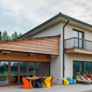 Deski elewacyjne wykonane z sosny bezsęcznej – ten gatunek drewna pochodzi z Nowej Zelandii i charakteryzuje się miodową barwą uzyskaną podczas procesu thermomodyfikacji. Warto wiedzieć, że sosna bezsęczna zaliczana jest według certyfikacji CATAS do 2 klasy odporności oznaczającej 20-25 lat żywotności bez zabezpieczania. Ewentualne malowanie stosuje się jedynie w celu zachowania barwy drewna bądź wybarwienia na inny kolor. Bez malowania deski elewacyjne Thermory pod wpływem promieni słonecznych patynują uzyskując szarą barwę. Fot. Thermory