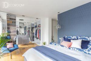 Wystrój sypialni z garderobą jest dowodem na to, że proste rozwiązania mogą być zarazem efektowne i funkcjonalne. Tak jak w pozostałych wnętrzach i tu dominuje kolor niebieski z elementami gołębiej szarości i bieli. Projekt i zdjęcia: Decoroom