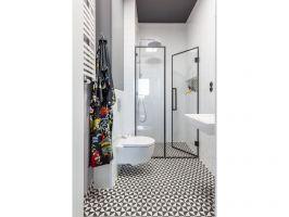 Podłoga i ściany w łazienkach zostały wykończone biało-czarnymi płytkami zdobionymi op-artowskim, geometrycznym deseniem. Projekt: Architekt wnętrz – Agata Koszelewska / Architekt Kuchni – Wioleta Cieślik (Decoroom)