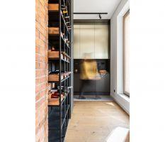 Niezbędny w wykończeniu loftu metal, m.in. listwy oświetleniowe, lampa nad stołem, regały na wino i książki, są w kolorze czarnym. Projekt: Architekt wnętrz – Agata Koszelewska / Architekt Kuchni – Wioleta Cieślik (Decoroom)
