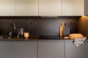 Nie można przeoczyć metalicznego wykończenia szafek kuchennych - na frontach zastosowano srebrzysty, metalowy laminat. Projekt: Architekt wnętrz – Agata Koszelewska / Architekt Kuchni – Wioleta Cieślik (Decoroom)