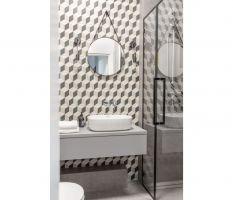 Podłoga i ściany w obu łazienkach wykończone są biało-czarnymi płytkami zdobionymi op-artowskim, geometrycznym deseniem. Projekt: Architekt wnętrz – Agata Koszelewska / Architekt Kuchni – Wioleta Cieślik (Decoroom)