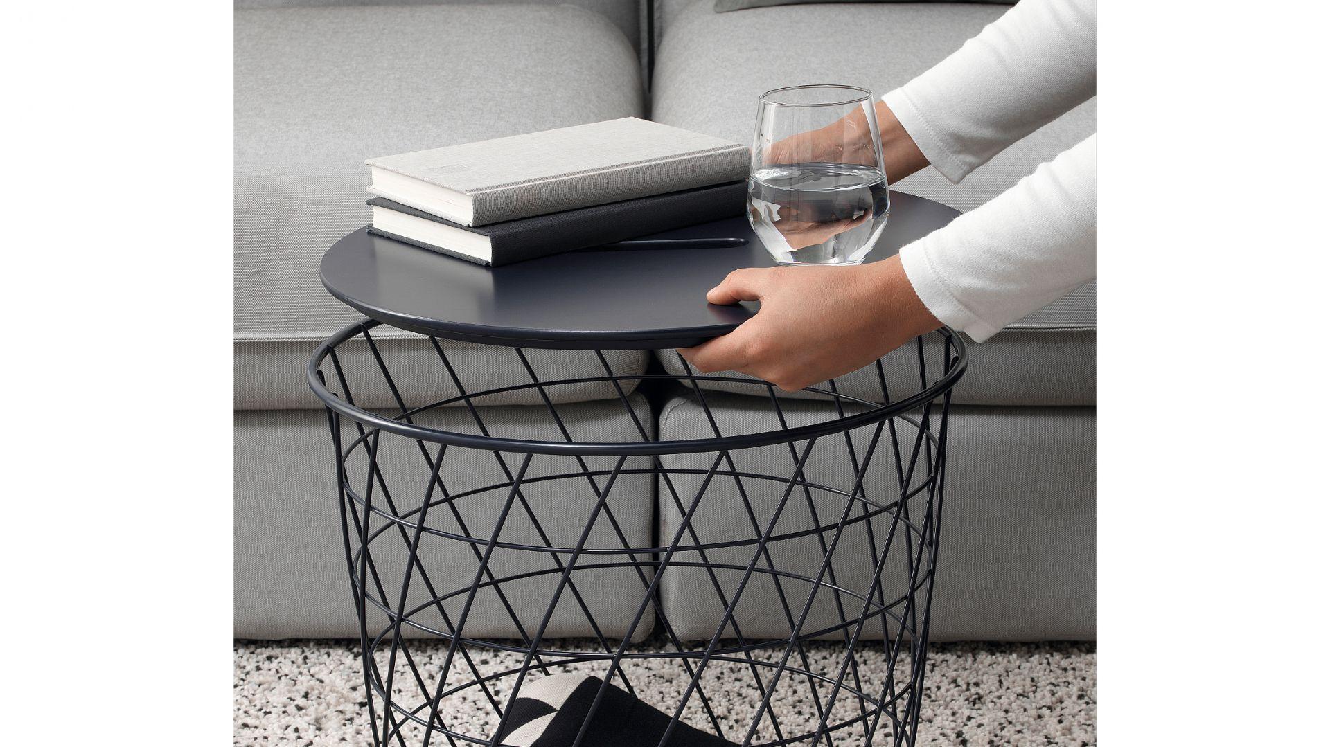 Stolik Kvistbro z miejscem do przechowywania, granatowy. Uchwyt umieszczony w blacie stołu ułatwia otwieranie i sięganie po przedmioty przechowywane w koszyku. Fot. IKEA