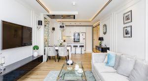 Piękny, jasny salon połączony z jadalnią i kuchnią. Duże okno i biel ścian sprawiają, że wnętrze wydaje się większe niż jest w rzeczywistości. Wystrój utrzymany w nowojorskim stylu to harmonijne zestawienie elementów klasyki i nowoczesnoś