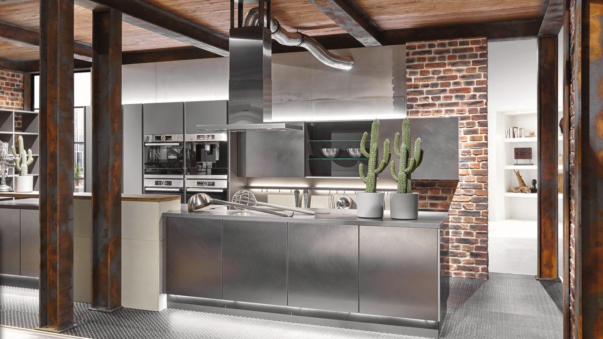 """Kuchnia industrialna. Lubi materiały o surowym charakterze – metal, beton, naturalne drewno ze śladami zużycia. Łączy prostą formę z nowoczesnymi rozwiązaniami. Dużą rolę w zabudowach kuchennych tego typu odgrywają odpowiednio dobrane dodatki – oświetlenie i akcesoria meblowe. Na zdjęciu: model """"Metal Concept"""" firmy Verle Kuchen. Fot. Verle Kuchen"""