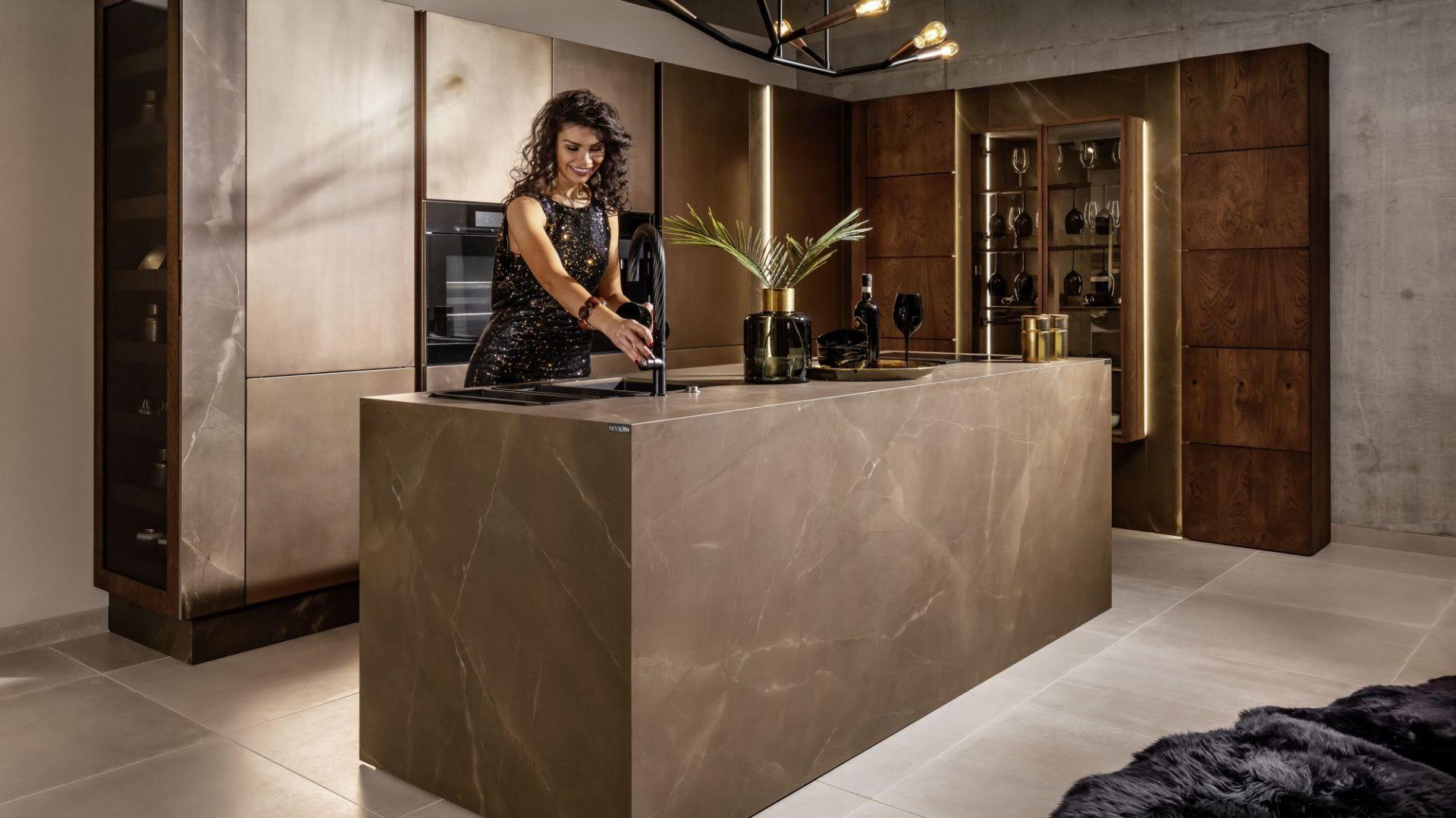 """Wyspa kuchenna. Jednym z najpopularniejszych sposobów na podkreślenie umownej granicy między przestrzenią kuchni a salonem jest zaprojektowanie wyspy. Wystarczy tylko dysponować pomieszczeniem o odpowiednio dużym metrażu i projektem, który dostosuje przebieg wszystkich niezbędnych instalacji do wymogów tego typu rozwiązania. W zależności od potrzeb domowników wyspa kuchenna równie dobrze może stać się strefą gotowania, zmywania lub przechowywania. Na zdjęciu: kuchnia """"Maronne"""" firmy Halupczok Kuchnie i Wnętrza. Fot. Halupczok Kuchnie i Wnętrza"""