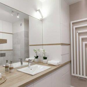 Obszerna szafka pod umywalką, a obok niej sięgający sufitu słupek na  pralkę, kosz na bieliznę i proszki do prania. Wszystko więc można schować, a na wierzchu (na narożnej półce) pozostawić tylko estetyczne rzeczy. Fot. Pracownia Architektoniczna MGN