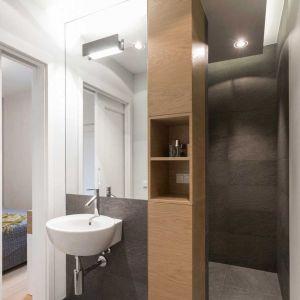 Przy wejściu do kabiny prysznicowej postawiono  wysoki słupek, który całkowicie rozwiązał problem przechowywania w tym niewielkim pomieszczeniu. Fot. Pracownia Architektoniczna MGN