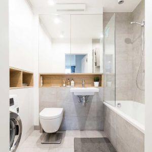 Nad umywalką wysoka szafka z lustrzanymi drzwiczkami, a przy ścianie obok niezwykle pojemna zabudowa od podłogi do sufitu. Ponieważ w pomieszczeniu nie zmieściłaby się szafa o głębokości 70 cm, zdecydowano się na płytszą. Nie udało się więc ukryć pralki. Nie szkodzi, łazienka i tak wygląda bardzo estetycznie. Fot. Pracownia Architektoniczna MGN
