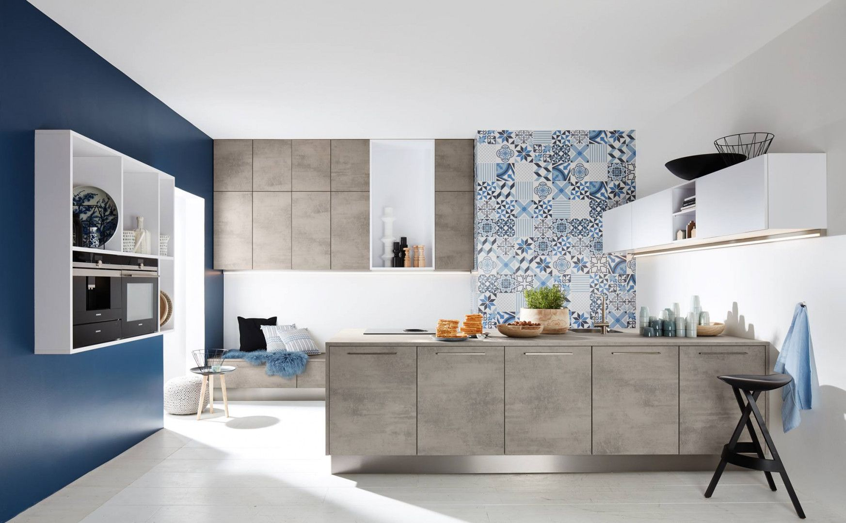 Szare fronty szafek półwyspu kuchennego nawiązują do modnej stylistyki imitującej beton. Idealnie współgrają z majoliką na ścianie. Fot. Nolte Kuchen