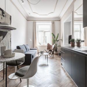 Kuchnia została przeniesiona do salonu, dzięki czemu udało się wydzielić sypialnię, cała przestrzeń nad blatem konsekwentnie została wyłożona lustrem, które powiększa optycznie salon. Fot. Scandilove