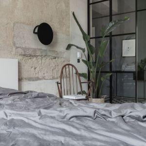 Jedna ze ścian w sypialni została oczyszczona do tynku i tworzy niepowtarzalny charakter w połączeniu z zielenią. Fot. Scandilove