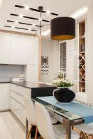 Obniżony i podświetlony ledowo sufit nad kuchennym półwyspem i stołem zapewnia odpowiednią ilość światła do pracy. Projekt i zdjęcia: Architetto