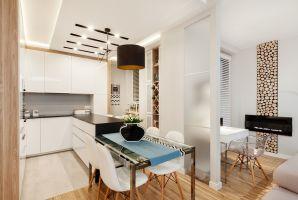 Zastosowanie ścianki przeszklonej mrożonym szkłem pozwoliło na funkcjonalne oddzielenie sąsiadującej z kuchnią jadalni od kącika do pracy. Projekt i zdjęcia: Architetto
