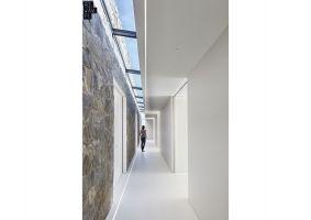 Dom Polny to dwie bryły, z których pierwsza została obłożona kamieniem polnym, natomiast drugą stanowi biały, parterowy pawilon. Obie łączy w całość długi korytarz na całej długości doświetlony przez świetlik. Projekt: 81.WAW.PL. Fot. Michał Przeździk/Budzik Studio