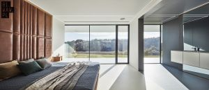 W sypialni właścicieli domu uwagę skupia duże, tapicerowane wezgłowie łóżka, które jest elementem wyróżniającym się pośród białych ścian. Projekt: 81.WAW.PL. Fot. Michał Przeździk/Budzik Studio