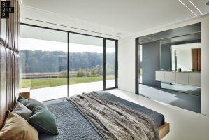 Oprócz okien, dużą ilość światła zapewniają także przeszklone drzwi prowadzące na taras. Sypialnia dodatkowo połączona jest z łazienką. Projekt: 81.WAW.PL. Fot. Michał Przeździk/Budzik Studio