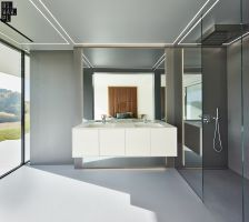 Część kąpielowa wyróżnia się szarą barwą, którą pokryte zostały ściany, sufit oraz podłoga. Dla rozjaśnienia tej przestrzeni zastosowano szklane i drewniane akcenty.  Projekt: 81.WAW.PL. Fot. Michał Przeździk/Budzik Studio