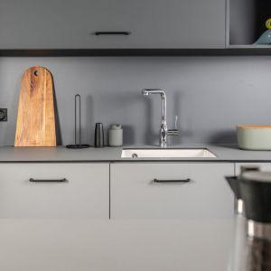 W kuchni zastosowano kolory z palety wyrafinowanych szarości – najciemniejszą tonację architekt wyznaczyła dla zabudowy kryjącej lodówkę oraz górnego rzędu szafek, jasny, popielaty odcień  wybrała na fronty dolnych szafek oraz wyspę. Projekt: Kasia Orwat. Fot. Dekorian Home