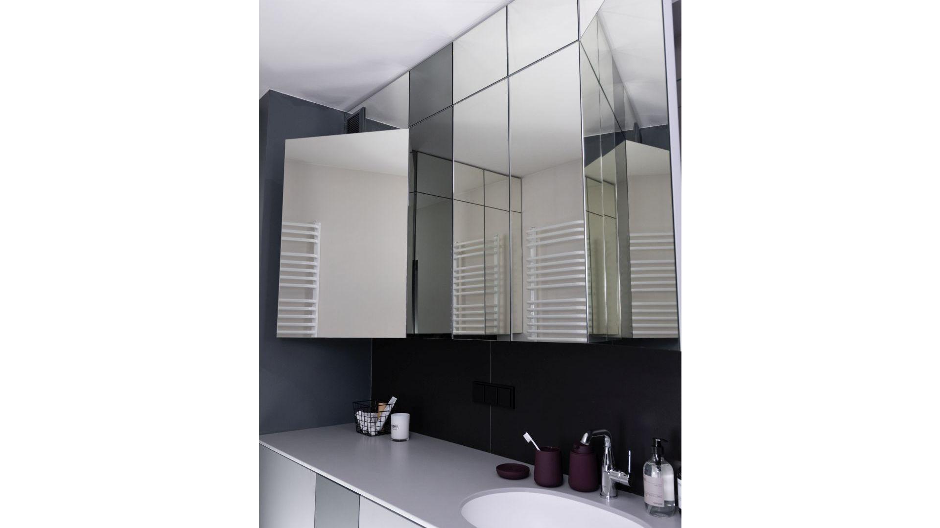 Moduły wiszących szafek mają lustrzane fronty i otwierają się rozłożyście jak toaletka – dzięki temu można się w nich przeglądać ze wszystkich stron. Projekt: Kasia Orwat. Fot. Dekorian Home