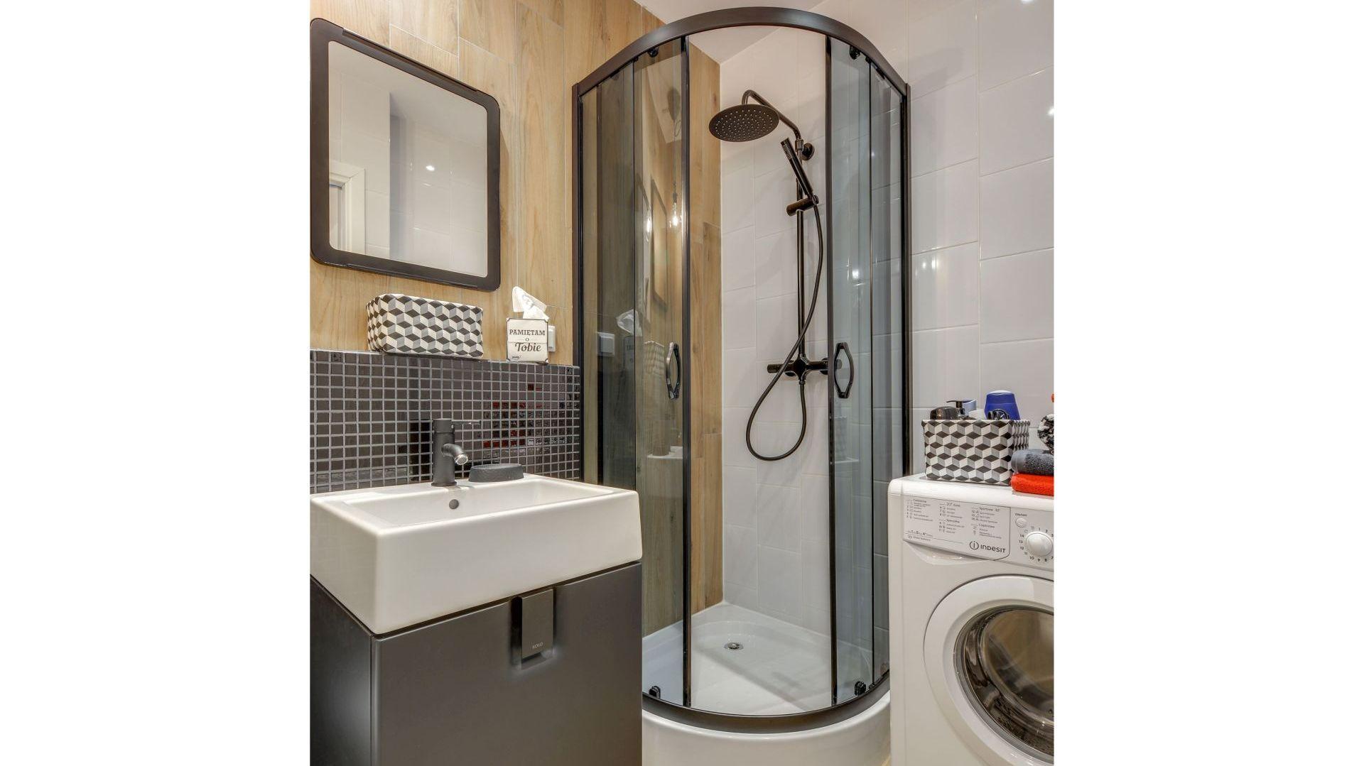 Deficyt przestrzeni w malutkiej kawalerce zdecydował o większości tu rozwiązań - kompaktowych meblach i kabinie prysznicowej. Projekt: Małgorzata Mataniak-Pakuła. Fot. Radosław Sobik