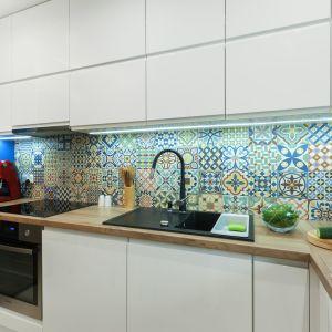 Charakter aranżacji podkreślają kolory: niebieska ściana oraz barwny patchworkowy wzór nad blatem. Projekt: Justyna Mojżyk. Fot. Monika Filipiuk-Obałek