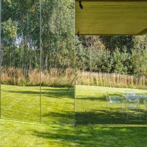 Przestrzeń dzienna przenika się więc rzeczywiście z ogrodem (otwarcie szklanych ścian), jak i iluzorycznie (odbicia w lustrzanych stalowych powierzchniach). Fot. Jakub Certowicz