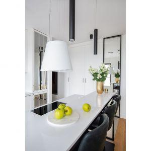Sięgające sufitu białe szafki wyglądają klasycznie, jest tu jednak coś, co jest w kuchniach spotykane bardzo rzadko – na niektórych frontach zamontowano lustra z frezami. Projekt i zdjęcia: Decoroom