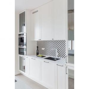 Biało-czarna kolorystyka i lustrzane powierzchnie sprawiają, że aneks kuchenny, choć niewielki, wygląda jasno i elegancko. Projekt i zdjęcia: Decoroom