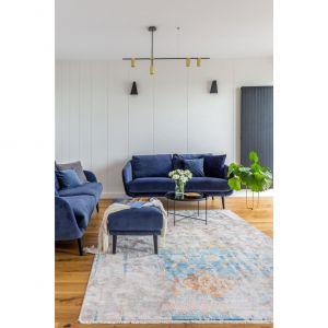 Głównym elementem ozdobnym salonu są sofy obite welurem w głębokim niebieskim odcieniu. Projekt i zdjęcia: Decoroom