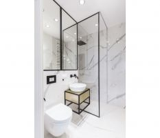 Jedna z dwóch łazienek bazuje na bieli i czerni, co dodaje jej elegancji i wyrazistości. Ściany zostały obite wielkoformatowymi płytkami ceramicznymi do złudzenia imitującymi marmur. Projekt i zdjęcia: Decoroom