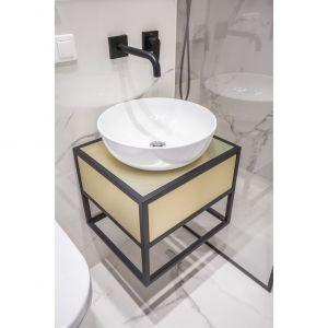 Nablatowa, nowoczesna umywalka w kształcie misy wspiera się na wiszącej szafce pokrytej laminatem powleczonym stalą w kolorze zgaszonego złota – kolejny ukłon w stronę glamour. Projekt i zdjęcia: Decoroom