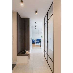 Wystrój mieszkania na warszawskiej Woli tworzy ciekawy miks stylów spiętych klamrą koloru – wyróżniającą się barwą jest tu niebieski w estetycznym otoczeniu bieli, szarości i akcentów czerni. Projekt i zdjęcia: Decoroom
