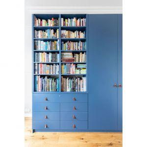 Pojemna szafa-biblioteczka kolorystycznie współgra z welurowymi kanapami. Projekt i zdjęcia: Decoroom