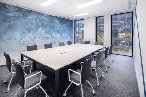 Kluczową decyzją było pozostawienie sufitów akustycznych oraz wyposażenie powierzchni w rozwiązania pomagające izolować źródła hałasu, jak budki telefoniczne, czy zamykane budki do spotkań i wideokonferencji. Projekt: Massive Design. Fot. Szymon Polanski