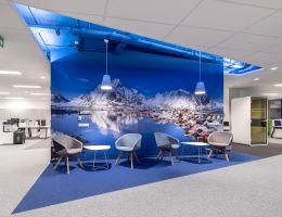 Aby stworzyć mniej formalny i cieplejszy klimat biura, architekci na tle wysp archipelagu Lofotów umiejscowili kącik z meblami miękkimi. Projekt: Massive Design. Fot. Szymon Polanski