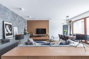 Jedyną dekoracją ścienną w salonie jest panel za telewizorem, który pięknie eksponuje rysunek drewna. Rolę dekoracyjną pełni także tynk strukturalny przypominający strukturę betonu. Projekt: Decoroom. Fot. i stylizacja: Marta Behling / Pion Poziom Fotografia Wnętrz