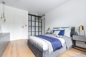 Wystrój przestronnej sypialni również opiera się o minimalistyczną koncepcję i monochromatyczne barwy. Projekt: Decoroom. Fot. i stylizacja: Marta Behling / Pion Poziom Fotografia Wnętrz
